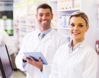 a male and female pharmacist smiling at the camera