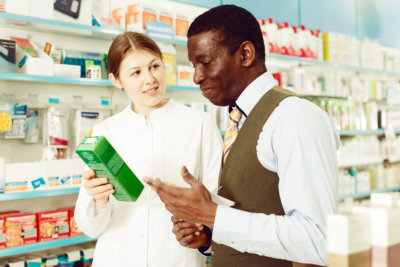 young pharmacist explaining prescribed medicine to the customer